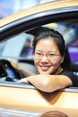 Frau mit brille lächelnd in ihrem auto — Stockfoto
