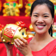 Asian woman hold a golden piggy bank — Stock Photo #23269458