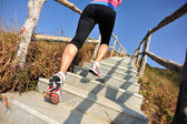 Sports woman running on mountain stairs — Photo