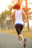 Asian woman jogging at tropical park — Foto Stock
