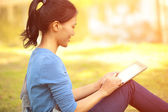 Student use tablet pc sit on grass — Stock Photo