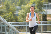 Asian woman running at modern city footbridge — Stock Photo