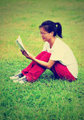 Studnet reading book on grass — Stock Photo
