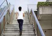 Woman running on escalator stairs — Stock Photo