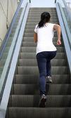 Woman running on escalator stairs — Stockfoto