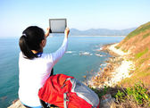 Woman stand on seaside rock and use digital tablet — 图库照片