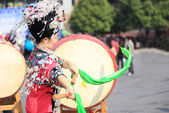 Miao nationality womon wearing silver accessories on hair and clothes beats a drum — Stock Photo