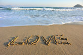 Love word drawn on sand — Stock Photo