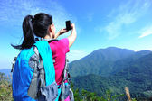 Hiking woman taking photo with phone — Stock Photo