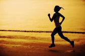Fitness frau joggen bei sonnenaufgang — Stockfoto