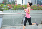 Asian woman running in the  city — Stock Photo