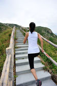 Woman running on mountain stairs — Stock Photo