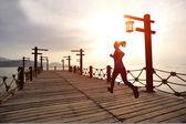 Woman running on wooden trail seaside — Стоковое фото