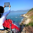 Hiking woman use digital tablet taking photo — Stock Photo #42133769