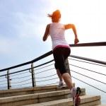 Woman running on stone stairs seaside — Stock Photo #42328211