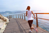 Woman running on wooden trail seaside — Stock Photo
