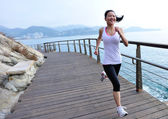 Woman running on wooden trail seaside — Stok fotoğraf