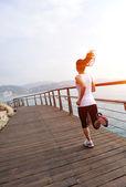 Woman running on wooden trail seaside — Stock Photo
