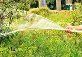 Jardinero con manguera de riego — Foto de Stock