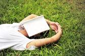 Student leesboek op gras — Stockfoto