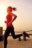 Woman running at seaside under morning sunrise — Stock Photo