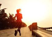 Sports woman running on wooden bridge seaside — Stock Photo
