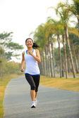 Runner athlete running at tropical park road — Stock Photo