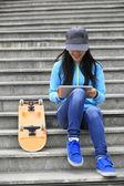 Skateboarder use digital tablet — ストック写真