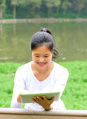 Woman use digital tablet in park — Stock fotografie