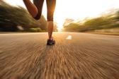 Runner athlete running on sunrise road — Stock Photo
