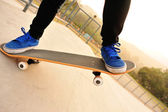 Feet in blue shoes skateboarding — 图库照片