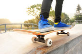 Feet in blue shoes skateboarding — Stock Photo