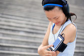 Woman athlete listening to music in headphones — Stock Photo
