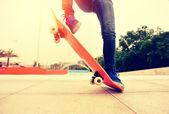 Skateboarding woman legs — Photo