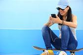 Woman skateboarder listening music — Stock Photo