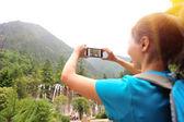 Woman tourist taking photo with smart phone — Stok fotoğraf