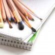 Colored pencils, notepad and paint brushes — Stock Photo