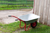 Wheelbarrow gardening tool on green grass — Stock Photo