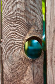 Hole in Wood Fence a hole in a old wooden fence — Stock Photo