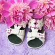 Children sandals and flowers on lilac carpet — Stock Photo