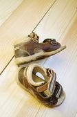 Children's sandals on wooden floor — Stock Photo
