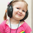Royalty-Free Stock Photo: Little beautiful girl in headphones listens to music