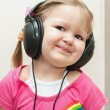 Little beautiful girl in headphones listens to music — Stock Photo