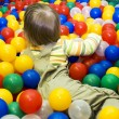 Baby girl in ball pit — Stock Photo