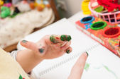 Colorful finger paints over white background — Stock Photo