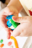 Child moulds from plasticine on table, hands with plasticine — Stock Photo