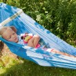 Little girl with toy sleeping on a hammock — Stock Photo