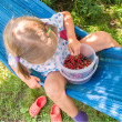 Stock Photo: Little girl is sitting on hammock and eating berries