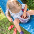 Llittle girl sitting on hammock and eating berries — Stock Photo