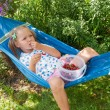 Little girl lying on a hammock, eating berries and dreams — Foto de Stock